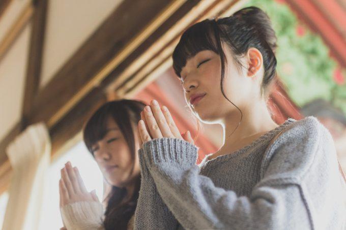 手を合わせてお祈りする2人の女性