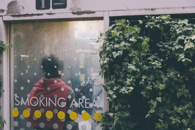スモーキングスペースでタバコを吸う人の背中