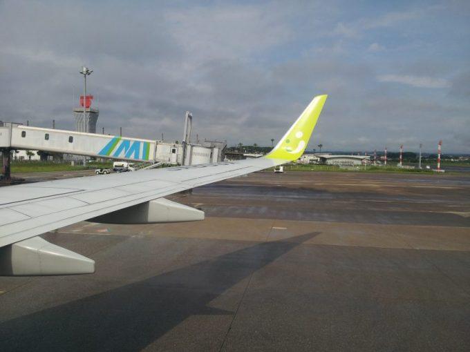 飛行機の中から撮影した地上に止まる飛行機の羽