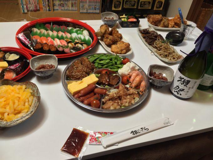 机に広げられたデリバリーのお寿司とオードブル