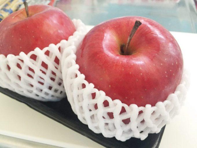 白いネットに入った2つのリンゴ