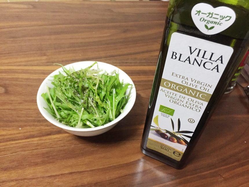 サラダにかけられたオリーブオイルと横に立つボトル