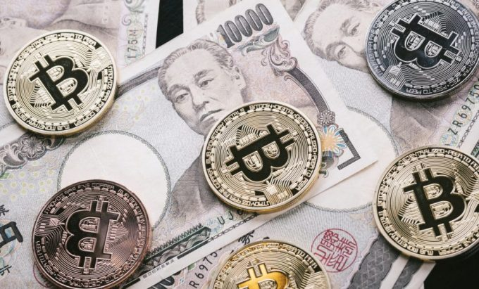 一万円札の上にのったビットコインを模した硬貨