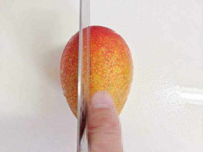 マンゴーの切る位置を確認する為に親指を置いて、種の位置をチェックしている状態