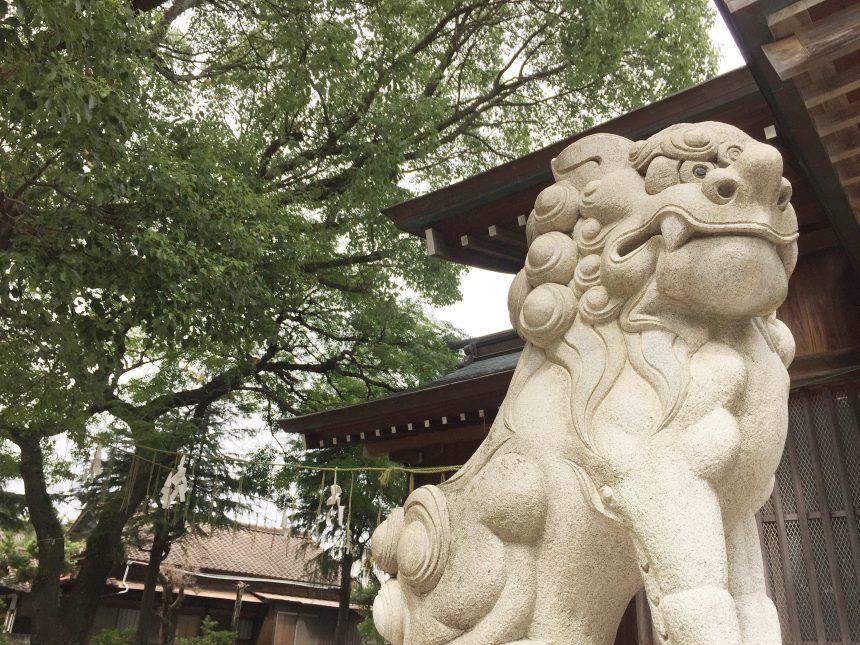 神社を背景に撮影した、吽形(うんぎょう)で口を閉じた狛犬