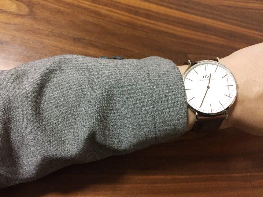 グレーのスーツに腕時計をつけた状態