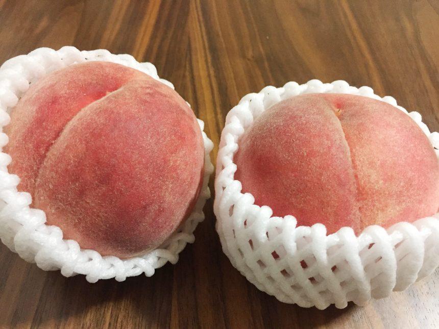 フルーツキャップに入って机に並んだ2個の桃