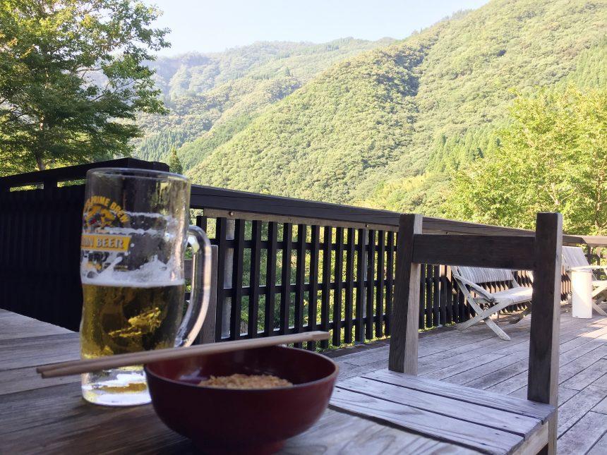 ウッドデッキにおかれたテーブルで生ビールと西米良コロッケを食べるの図。