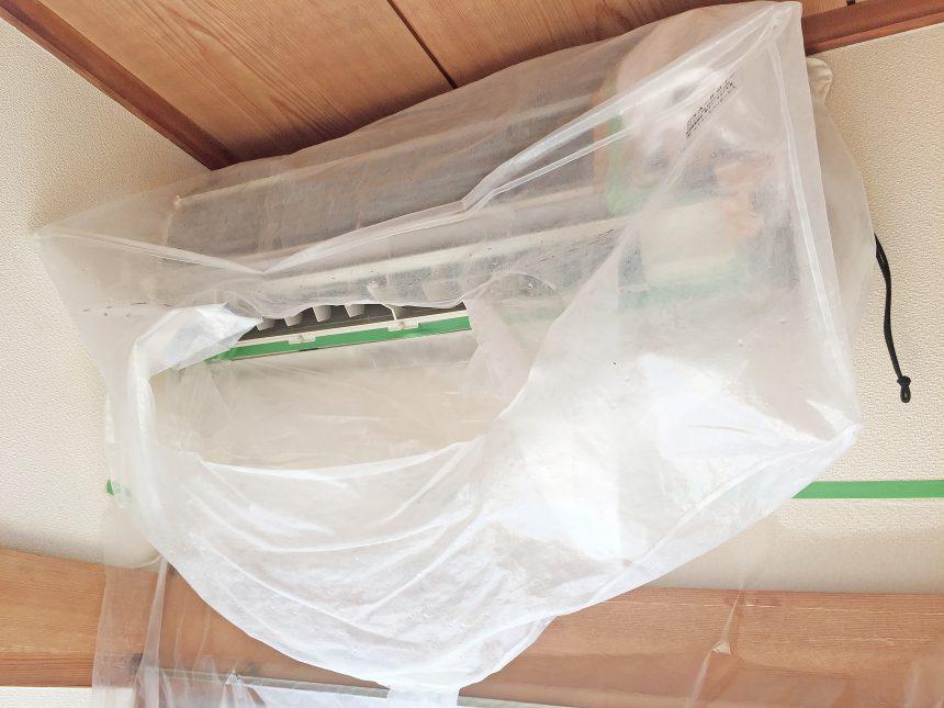 エアコンクリーニングを業者に依頼し、掃除の前準備でカバーをかけられた状態