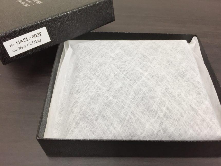 箱を開け、白い袋に入った財布。UNITED ARROWS(ユナイテッドアローズ) ◆UADB サフィアーノ 2つ折 ウォレット。箱に記載された(Navy × LT.Gray)
