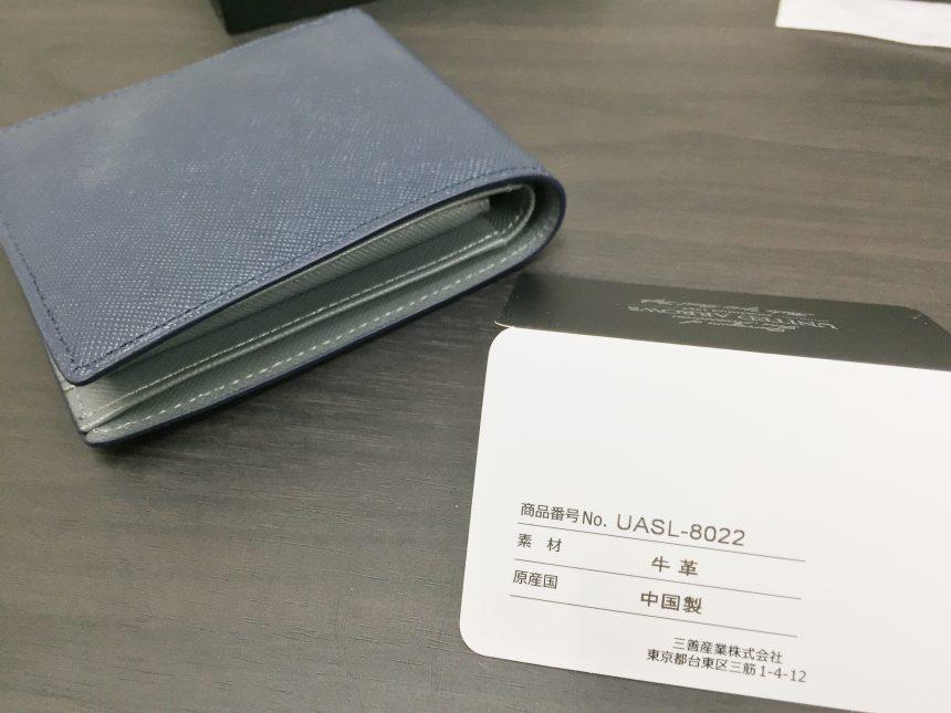 タグに書かれた財布の情報。商品番号No.UASL-8022、素材牛革、原産国中国製、三善産業株式会社