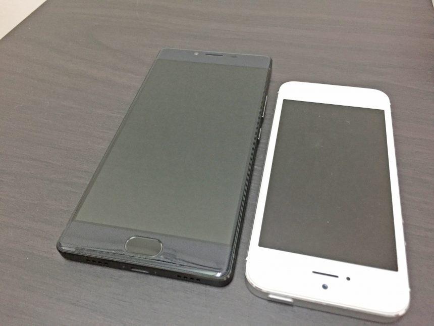 フリーテルREI(黒)とiPhone5(白)を机に並べて大きさを比較した状態