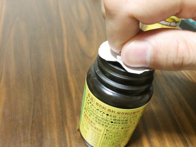 ネイチャーメイドの蓋の開け方。出っぱったフィルムを持ち、ねじるようにあける。