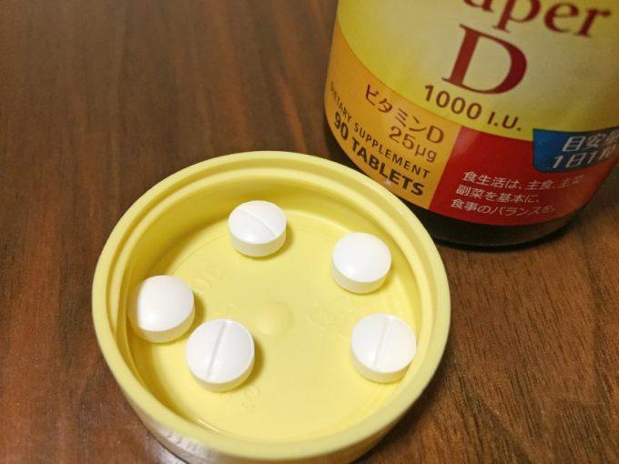 ボトルのフタに入れたビタミンD錠剤5粒