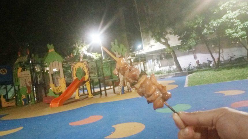 雙城街夜市の近くの公園で焼き鳥を食べる