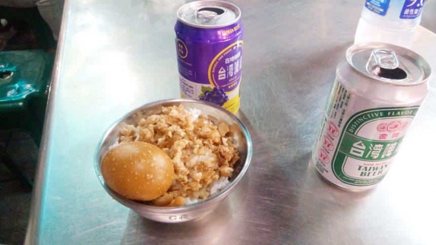 銀色のテーブルの上にのった魯肉飯(ルーローハン)と台湾ビール&フルーツビール