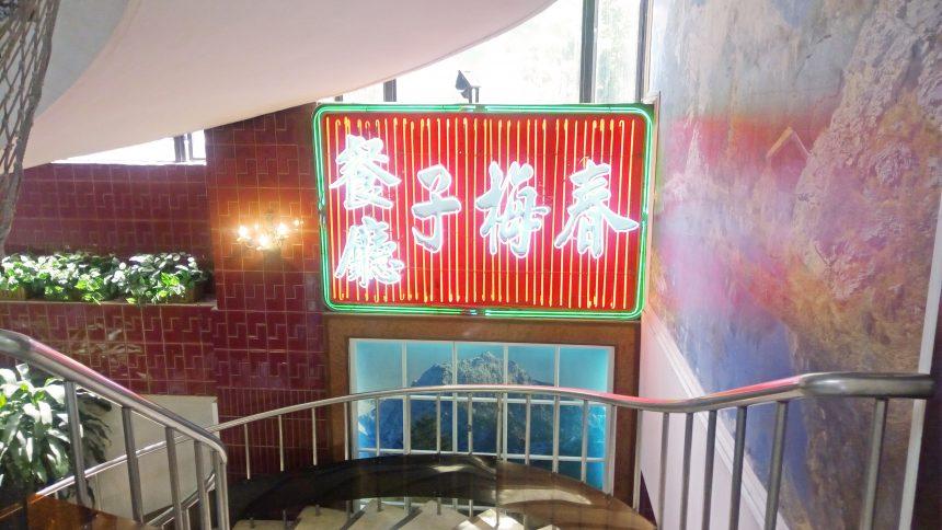 春梅子餐廳の看板。地下の店内に続く螺旋階段