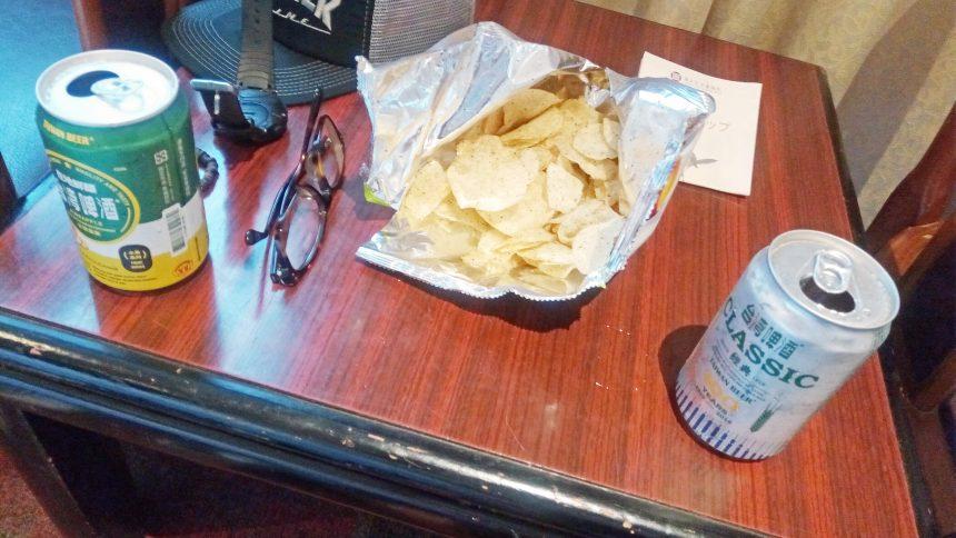 机に広げたビールとポテトチップス