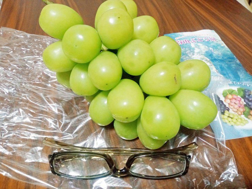 シャインマスカットの大きさ比較のため置いたメガネとマスカット。
