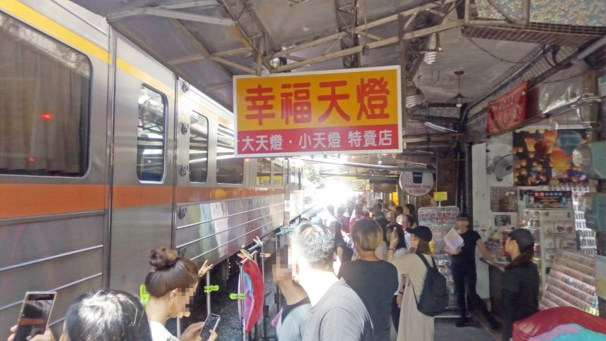 スレスレを走る列車と商店と人ゴミ