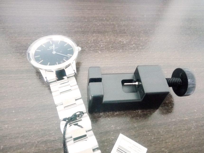 腕時計と、腕机に置いた時計のコマを調整する道具