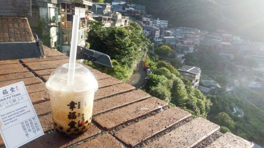 九分の高台を背景にしたタピオカミルクティーとおみくじ結果